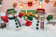 Snowman stand among pile of snow at silent night with a light bulb,Merry christmas and new year night. Stock Images