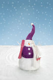 Snowman is standing in the snow with skis Royalty Free Stock Photography