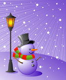 Snowman stands under a lamp on a snowy evening Stock Photo