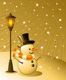 Snowman stands under a lamp on a snowy evening Royalty Free Stock Images