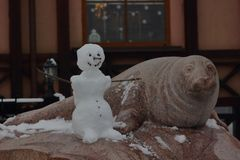 Snowman with a stone figure of walrus royalty free stock photo