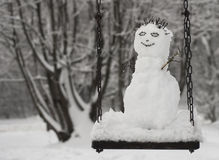 Snowman on swing. Cute snowman on the swing at winter Stock Images