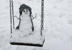 Snowman on swing Royalty Free Stock Image