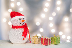Snowman with three boxes. Happy snowman and red, green, and golden gift boxes on the snow with lights background Royalty Free Stock Photos