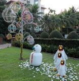Snowman and three penguins on a green lawn, garden sculpture, palm trees and decorative trees royalty free stock photo
