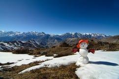Snowman on top of a mountain with mountain range at the background. Snowman on top of a mountain with snowy mountain range at the background Royalty Free Stock Photo