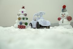 Snowman and toy car on snowy background. Snow sculpture with smiley face on winter day. xmas and new year. Christmas tree and present box on grey sky. Holidays Royalty Free Stock Photography