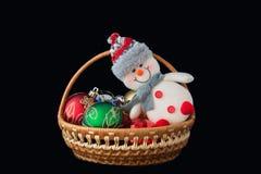 Snowman toy, Christmas ball, basket on a black background. Stock Photo
