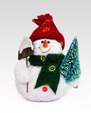 Snowman toy figure with christmas tree. Snowman toy figurine holding a shovel and a Christmas tree Royalty Free Stock Images
