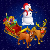 Snowman and two reindeer with sledge with gifts Royalty Free Stock Photos