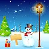 Snowman under Lamp post. Illustration of snowman under lamp post in christmas night with santa flying in sledge Stock Photo