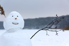 Snowman Waving in Greeting before a Frozen Lake royalty free stock photo