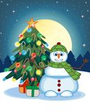 Snowman Wearing A Green Hat And Green Scarf Waving His Hand With Christmas Tree And Full Moon At Night Background For Your Design Stock Photo