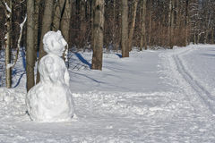 Snowman   in the winter woods. Royalty Free Stock Image