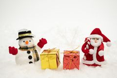 Free Snowman With Gift Box Is Standing In Snowfall, Merry Christmas And Happy New Year Concept Stock Photo - 131456420