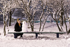 Snowman and woman at night park Stock Images