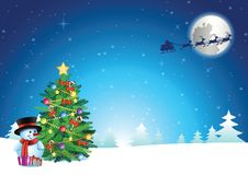 Snowman and xmas tree stand on snow while santa claus fly away a royalty free stock photography