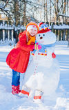 Snowman and young girl. Snowman and  happy young girl Stock Photo