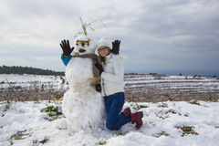 Snowman and young girl Stock Photo
