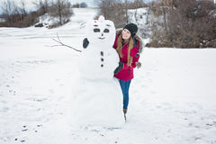 Snowman and young girl in winter season Royalty Free Stock Image