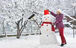 Snowman and young girl Royalty Free Stock Photos