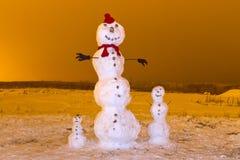 Snowmanfamilj i vinterlandskap Arkivfoton