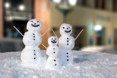 Snowmanfamilj som dekoreras med kaffekorn och träpinnar Royaltyfria Bilder