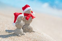 Snowmans couple at sea beach in christmas hat. New years holiday. Smiley sandy snowmans couple at sea beach in christmas hat. New years holiday in hot countries Stock Photography