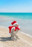 Snowmans couple at sea beach in christmas hat. New years holiday Stock Images