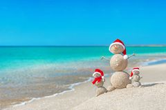 Snowmans family at sea beach in santa hat. Royalty Free Stock Photography