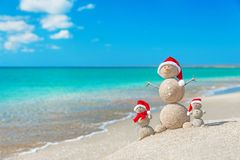 Snowmans family at sea beach in santa hat.