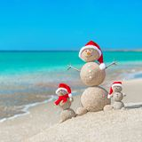 Snowmans family at sea beach in santa hat. Stock Images