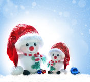 Snowmans in red hat on a snowy background Royalty Free Stock Photography