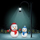 Christmas snowmans pillar and night city Stock Photo
