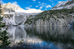 Snowmass Lake in Jun with Snow still on top of the Basin with a large reflection over the lake Royalty Free Stock Images