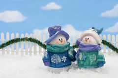 Snowmen. Two snowmen on a white picket fence with garland on a  sky background Royalty Free Stock Photography