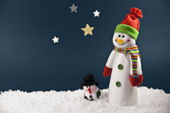Snowmen. Two Snowmen against a Blue Night Sky with room for your writing Royalty Free Stock Photos