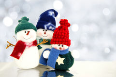 Snowmen. Family of snowmen with twinkling silver light background Royalty Free Stock Photography