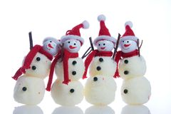 Snowmen. Funny, smiling snowmen  on a white background Royalty Free Stock Photography