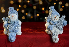 Snowmen. Snowman christmas ornaments with blurred christmas tree lights in the background (shallow depth of field on snowmen Stock Photography
