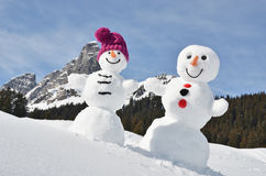 Snowmen against Swiss Alps. Funny snowmen against Swiss Alps Royalty Free Stock Images