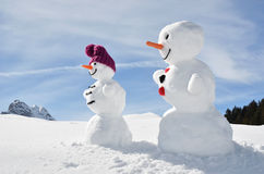 Snowmen against Swiss Alps Stock Photography