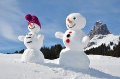 Snowmen against Swiss Alps Royalty Free Stock Photos