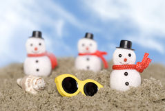 Snowmen on the beach. Christmas ornament snowmen make their way across the beach in a tropical theme with a shell and sunglasses.  Good use for Christmas holiday Royalty Free Stock Photo