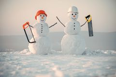 Snowmen builders. Happy holiday and celebration. New year snowman from snow with saw. Snowman builder in winter in helmet. Building and repair work. Christmas stock images