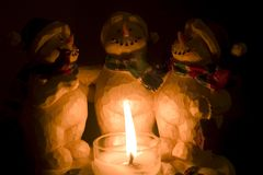 Snowmen candle holder. 3 snowmen gathered around a lit candle royalty free stock image