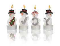Snowmen Candles Spell Joy. Four lit snowmen candles spell out the word JOY Stock Photography