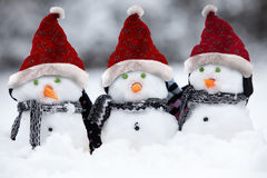 Snowmen with Christmas hats. Snowmen wih Christmas hats and scarfs sat in the snow Stock Photos
