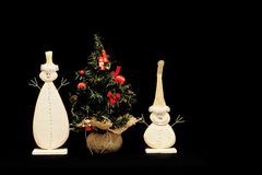 Snowmen and Christmas tree. A view of two small white snowmen and a toy Christmas tree on a black background Stock Photo