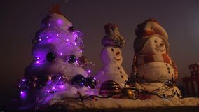 Snowmen Christmas tree, decoration toys. Toys in snow. Christmas presents from Santa. Snowmen wait for Santa and. Celebrate Christmas in mountains. New Year`s stock footage